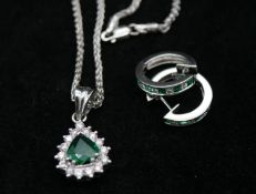 An 18 carat white gold emerald and diamond pendant and chain with emerald and diamond hoop earrings.