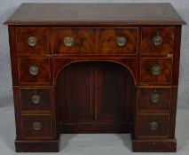 A Georgian flame mahogany and satinwood strung kneehole desk with twin brass carrying handles and an