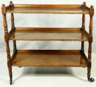 A Georgian mahogany three tier buffet with turned supports on brass wheel casters. H.102 W.107 D.