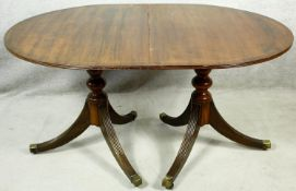 A Georgian style mahogany dining table with extra leaf on twin pedestal reeded swept supports