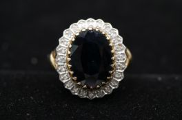 A yellow metal (tested as 9ct gold) sapphire and diamond cluster ring, set to centre with an oval
