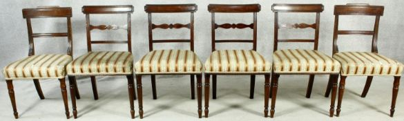 A matched set of six late Georgian mahogany dining chairs with bar backs above stuff over seats on