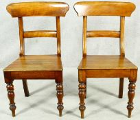 A pair of mid Victorian mahogany bar back hall chairs with panel seats on turned tapering bulbous