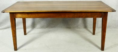 A French Provincial style refectory dining table with planked top and extension leaf with frieze