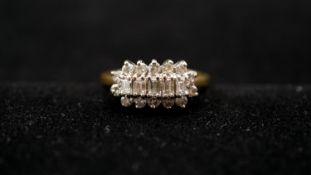 An 18 carat yellow gold and diamond set cluster ring. Set with five rectangular baguette cut