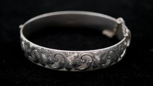 A Georg Jensen engraved silver clip bangle, engraved with a stylised foliate and floral design.