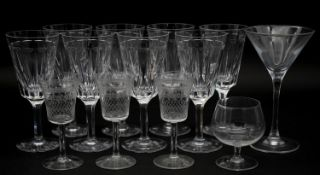 A collection of thirteen glasses to include eight wine glasses with faceted design along with