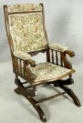 A late 19th century carved mahogany framed American rocking chair with spring mechanism. H.100 W.