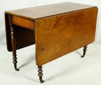 A 19th century mahogany drop flap dining table on turned tapering supports terminating in brass
