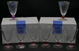 Three sets of Studio Nova drinking glasses, each with different coloured ball stem, one with red,