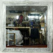 A wall mirror in distressed floral decorated silvered frame. H.148 W.144cm