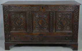 A 17th century carved oak coffer fitted with base drawers on shaped bracket feet. H.84 W.138 D.52cm