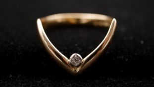A 9ct yellow gold and diamond wishbone ring, set with a round brilliant cut diamond in a rubover