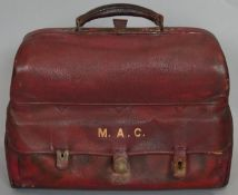 A lockable red leather travelling men's vanity case. Contains ivory glove stretchers, silver