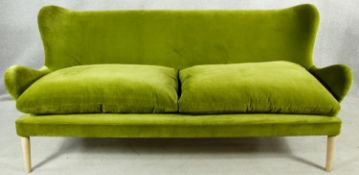 A retro style Designers Guild two seater sofa in velour upholstery on shaped tapering supports. H.92