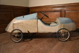 An early 20th century push along toy racing car of sheet metal on a wooden frame. H.56 W.160 D.42cm