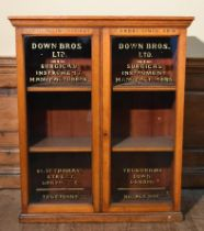 A late 19th century Down Bros Ltd light oak display cabinet; surgical instrument makers since