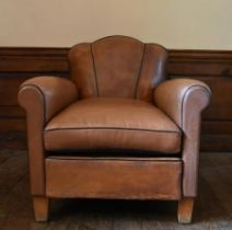 A vintage club armchair in piped and studded tan leather upholstery on block supports. H.82 W.78 D.