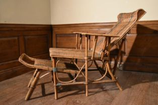 A vintage bamboo framed and rattan woven folding veranda armchair fitted with slide out foot rest.