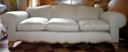 A three seater sofa with shaped back and apron upholstered in piped and studded calico on carved