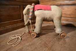 An early 20th century pull along child's toy elephant on metal base and wheels. H.56 L.75 W.40cm