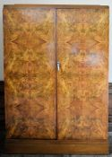 An Art Deco burr walnut gentleman's wardrobe by Compactom Ltd with patent label and travelling