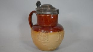 An antique silver lidded Doulton Lambeth tobacco jug with relief decoration. Lid hallmarked: WE,