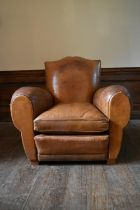 A vintage club armchair in piped tan leather upholstery. H.87 W.97 D.97cm (seat height.40cm)