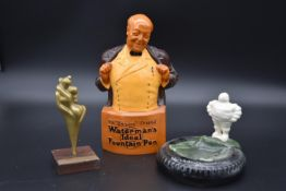 A ceramic Waterman's pens advertising bust along with a vintage Michelin Man ashtray and a brass