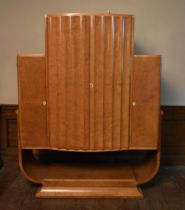 An Art Deco burr walnut cocktail cabinet with ribbed central panel doors enclosing glazed and lit