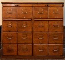 A large vintage oak filing cabinet fitted with a bank of sixteen drawers and a pair of slide out