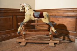An early 20th century carved and painted Triang rocking horse on swing action oak platform base. H.