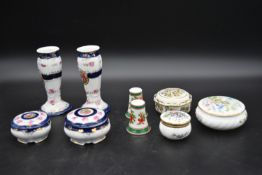 A pair of Continental porcelain candlesticks (chips to rim) with two matching lidded pots, three