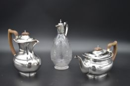 A vintage silver plated coffee pot and the matching teapot and a cut crystal claret jug with
