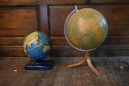 A vintage German light up globe on tripod stand along with a 1950's vintage globe on metal base. H.