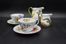 A pair of large Spode floral decorated tea cups and saucers and two Royal Collection jugs. H.14 W.