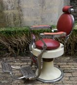 A vintage chrome adjustable barbers chair on metal base in faux leather upholstery with swivel