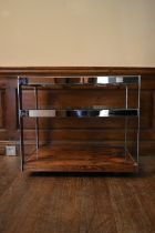A Merrow Associates chrome framed drinks trolley with plate glass tiers on casters. H.64 W.73 D.46cm