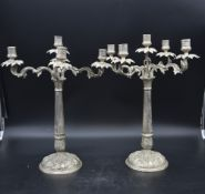 A pair of silver plated five branch table candelabras with palm decorated sconces on scrolling