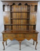 A Georgian style oak dresser with open plate rack fitted with cupboards above three drawers with