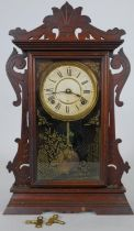 A late 19th century American walnut cased mantel clock with enamel dial and eight day movement by