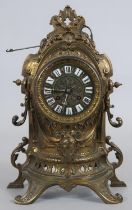 A French style brass mantel clock in scrolling Rococo case with enamel Roman numerals and eight
