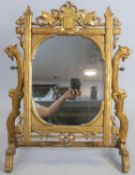 A large late 19th century carved giltwood swing toilet mirror in naturalistic foliate frame with