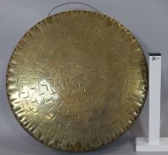 A large oriental hammered brass gong with carrying handle. D.45cm