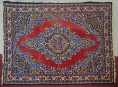 A Persian style carpet with central medallion on a burgundy ground within naturalistic floral