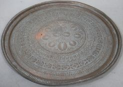 A large brass Eastern engraved tray or table top. D.95cm