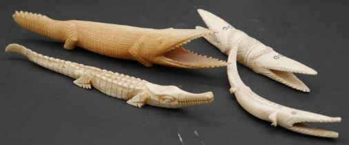 A collection of four carved bone crocodile figures. L.20cm