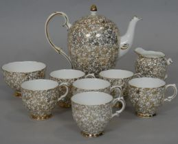 A Imperial bone china 24 carat gold plated floral design coffee set with, coffee pot, six cups,