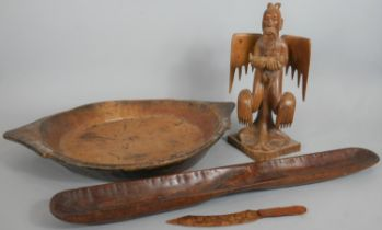 A collection of carved wooden items. Including an oriental carved statue of a deity, a two handled