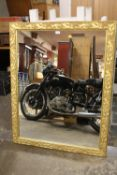A LARGE GILT FRAME WALL MIRROR WITH RELIEF DETAIL TO THE FRAME, OVERALL SIZE INC FRAME 98.5CM X
